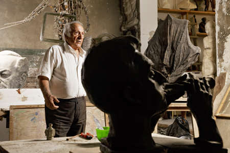 Senior sculptor among statues in his workshop Stock Photo - 16469288