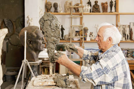 sculptor: Senior sculptor making sculpture putting clay on wire skeleton sideview
