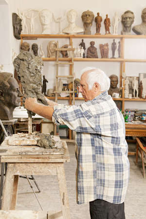 Senior sculptor making sculpture putting clay on wire skeleton profile view Stock Photo - 16469302