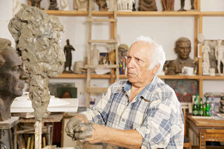 Elderly sculptor making sculpture putting clay on wire skeleton Stock Photo - 16469283