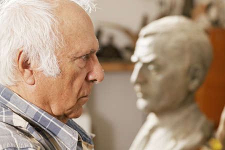 Senior man standing against statue profile view closeup Stock Photo - 16469297