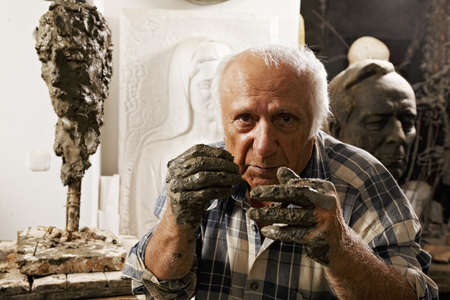 Elderly sculptor in studio holding hands at his face Stock Photo - 16469295
