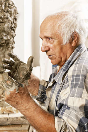 Elderly sculptor in studio holding hands at his face profile view Stock Photo - 16469304