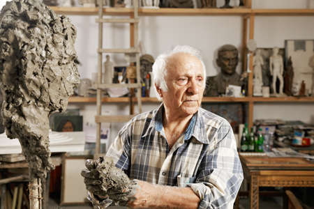 Senior sculptor standing in workshop against sculpture and kneads clay Stock Photo