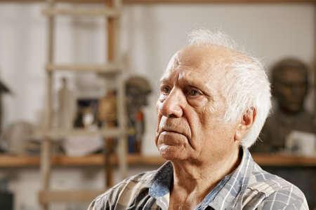 Elderly man in sculptors workshop looking sideways Stock Photo - 16469191