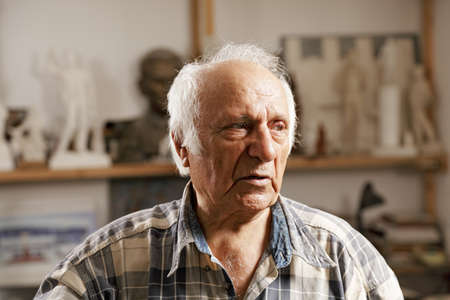 Senior man in sculptors workshop looking sideways photo