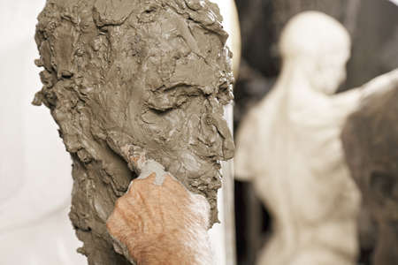 Sculptors forefinger on sculpture with statue on background Stock Photo
