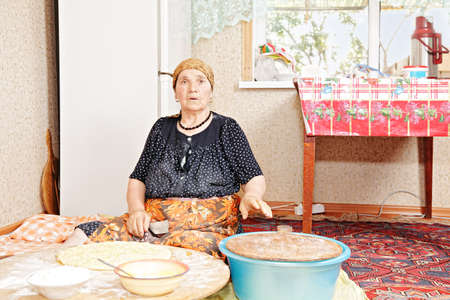 Senior woman baking bread at home kitchen while sitting on rug against fridge Stock Photo - 16731621