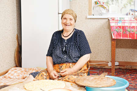 Happy senior woman baking bread at home kitchen while sitting on rug against fridge photo