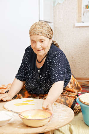 Senior woman sitting on the kitchen floor and taking the bowl with ghee while making homemade bread photo