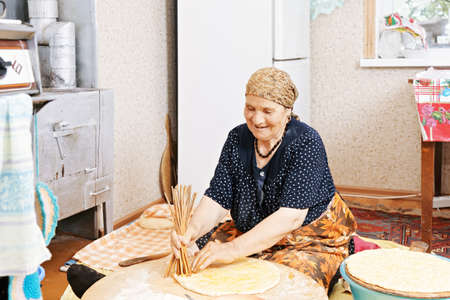 shef: Senior woman sitting on kitchen floor and holing the bread with bunch of sticks to prevent it inflation while baking Stock Photo