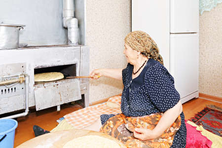 Senior woman sitting on kitchen floor and putting bread into oven photo