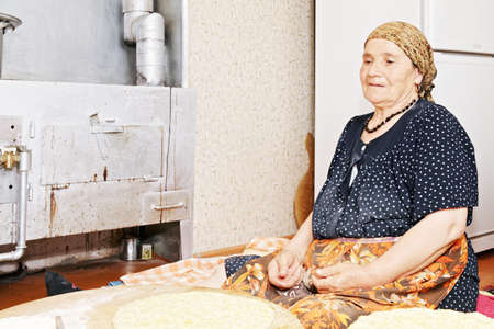Pensive senior woman baking bread at home kitchen while sitting on rug against fridge photo