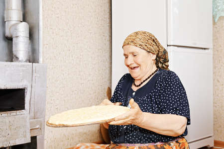 Senior woman with homemade bread preparing to bake it in oven photo
