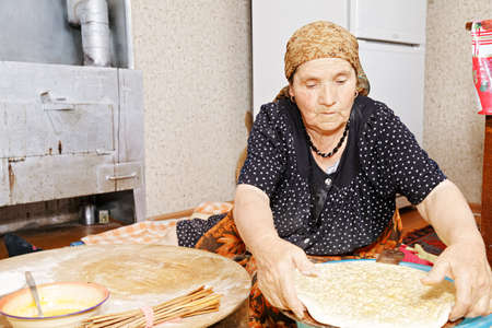 Senior woman sitting on kitchen floor and putting raw bread on wooden board for baking photo