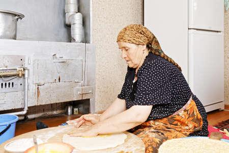 haciendo pan: La mujer mayor se sienta en el suelo de la cocina y cubriendo ghee pan casero