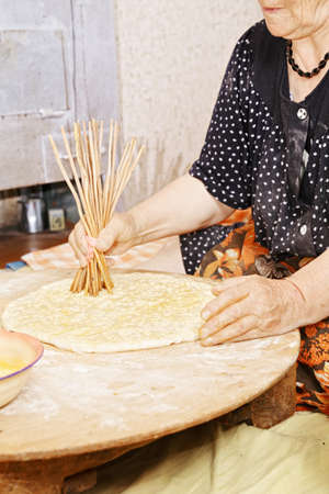 Senior woman making holes in bread with wooden sticks photo