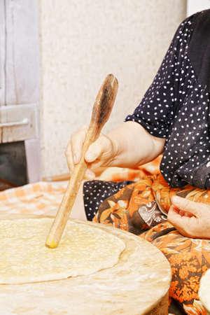 Senior woman in kitchen flattening bread with spatula Stock Photo - 16731613