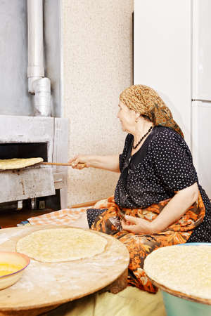 Senior woman sitting on kitchen floor gets a bread from the oven photo