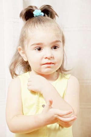 looking sideways: Little cute brunette caucasian girl in yellow dress looking sideways Stock Photo