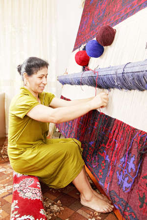 Smiling carpet weaver at work in workshop sideview photo Stock Photo - 17415232