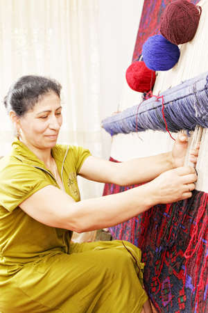 Carpet weaving woman at work in workshop sideview closeup photo photo