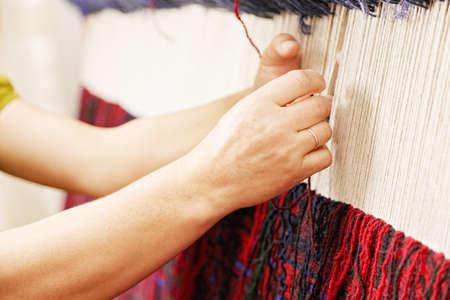 Woman hands weaving carpet closeup photo Stock Photo