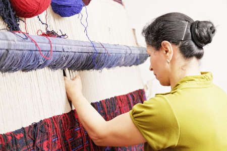 loom: Weaver holding threads while working on loom closeup sideview photo Stock Photo