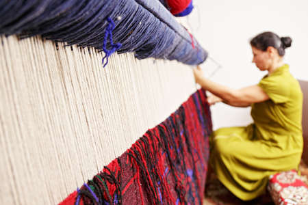 Loom for hand weaving carpet with woman working at backstage photo