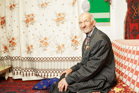 contented: Senior contented man on sofa at home
