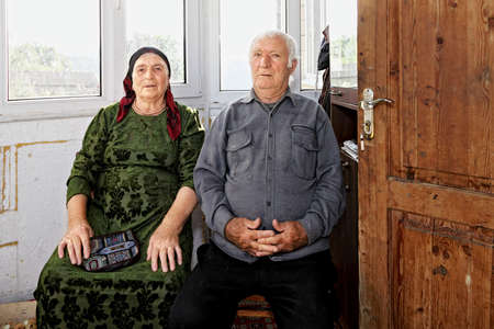spouses: Senior spouses sitting at home against big window