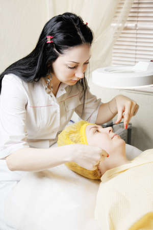 threading hair: Brunette beautician makes threading hair removal procedure to middle-aged caucasian woman laying down in chair
