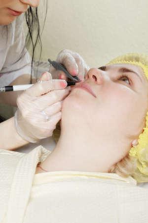 Caucasian female patient having electric skin care procedure