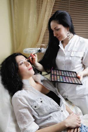 Beautician handles womans eyebrows at visage procedure