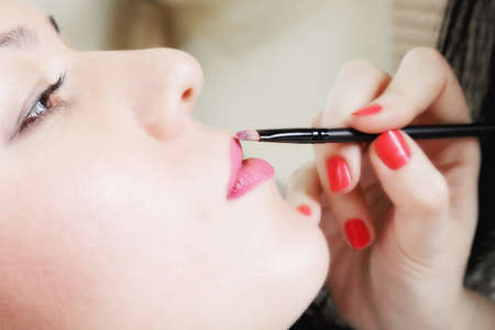 Pink lipstick applied to young woman by beautician photo