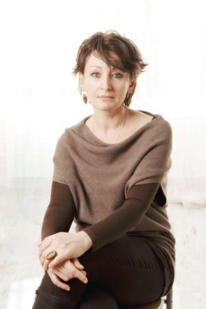 Serious middle aged woman in brown sweater against light background