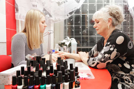 Manicurist at work polishing senior woman's fingernails Stock Photo - 18357854