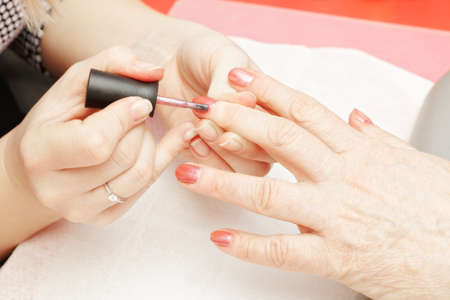 Senior womans hand being covered with red polish Stock Photo