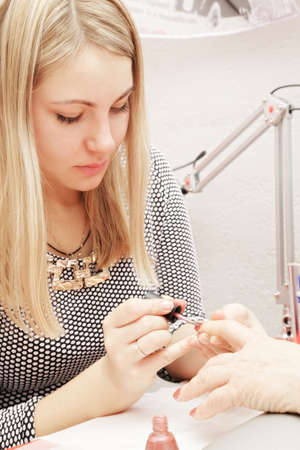 Beautician at work polishing senior womans fingernails