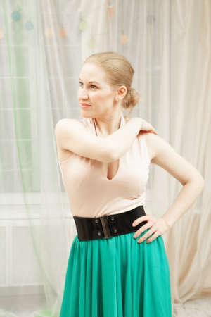 Young blonde dancer wearing green skirt standing in static pose and looking sideways Stock Photo