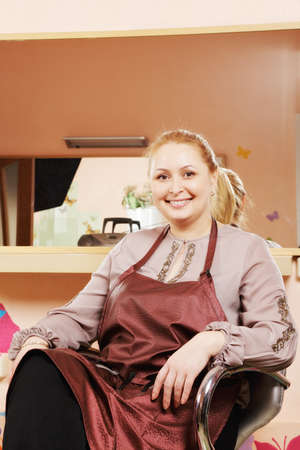 Smiling blonde hairdresser sitting in chair against mirror Stock Photo - 18466375