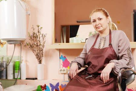 Blonde hairdresser sitting in chair against mirror Stock Photo - 18466381