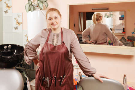 Blonde hairdresser standing at the chair against mirror Stock Photo - 18466374