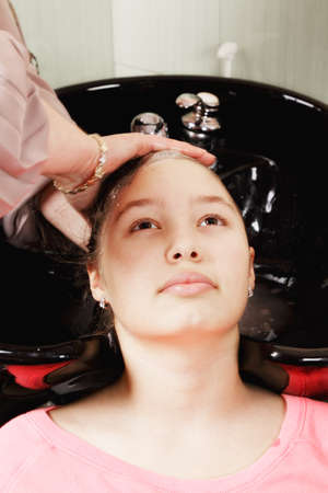 Hairdresser washing teenage girl head in basin Stock Photo - 18496393