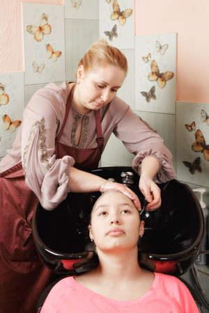 Hairdresser at work washing head of teenage girl Stock Photo - 18496434