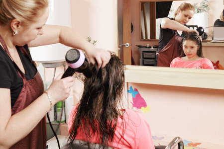 Hairdresser drying teenager girl's hairs against mirror Stock Photo - 18496408
