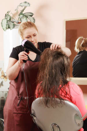 Hairstylist drying teenager girl's hairs against mirror Stock Photo - 18496420
