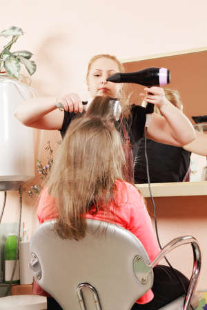 Middle-aged caucasian female stylist at hairdo process Stock Photo - 18496425