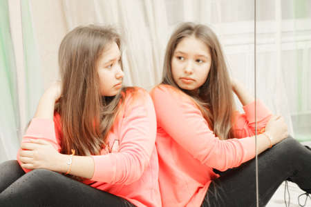 Teenage girl looking at her reflection in mirror closeup photo photo