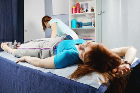 lymphatic drainage: Redhead woman laying down on couch during pneumatic compression massage procedure used for lymphatic drainage improving
